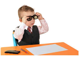 kleiner junge sitzt ab tisch und sieht durch die brille