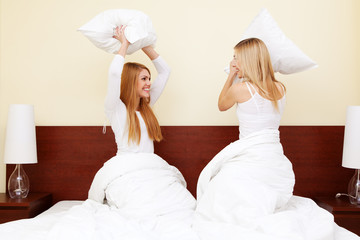 Two girld having a pillow fight in bedroom
