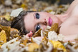 Beautiful young woman lying autumn leaves