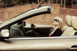 Young blond woman driving convertible car
