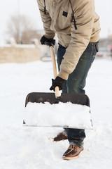 closeup of man shoveling snow from driveway