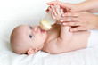 adorable child drinking from bottle. 5 months old girl.