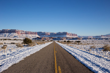 Open road in snow covered landscape with mountain range