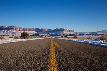 Empty road with snow capped mountains