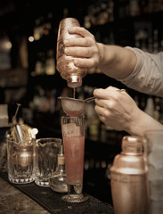 Bartender is straining cocktail