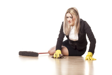 nervous and tired business woman with a broom and gloves