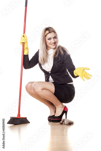 smiling business woman with a broom and gloves