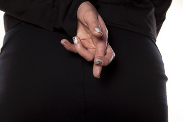 A woman holds Crossed fingers behind her back