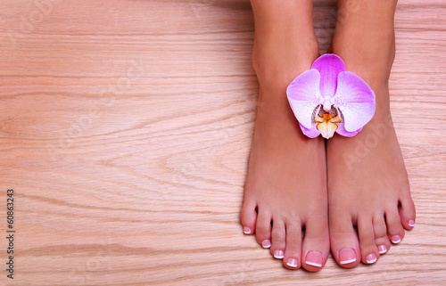 Pedicure with pink orchid flower on wooden background. Beautiful