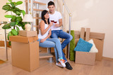 Young couple celebrating moving to new home sitting on stairs