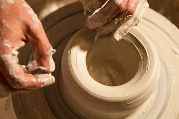 Hands working on pottery wheel , close up