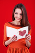 Attractive woman with postcard, on red background