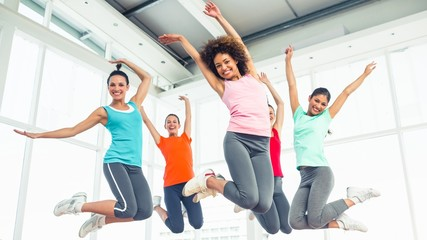 Fitness class and instructor jumping in fitness studio