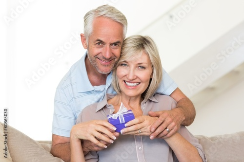Smiling mature man surprising woman with a gift on sofa