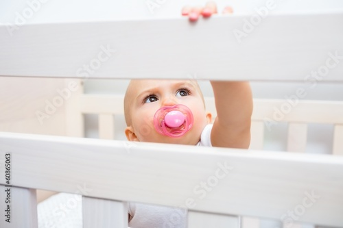 Cute baby with pacifier in mouth in the crib