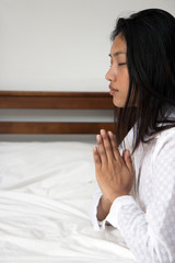 Young woman praying in bed