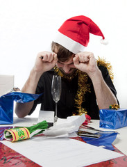 Man in Santa Claus hat loooking depressed about money