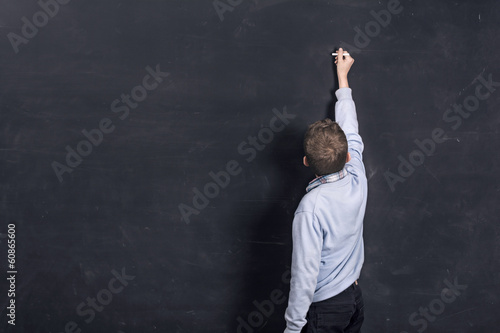Boy standing in front of chalkboard writing