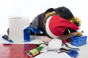 Man in Santa Claus hat depressed about his finances.