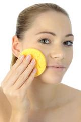 Frau reinigt Gesicht mit Schwamm