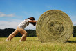 Woman pushing straw bale on