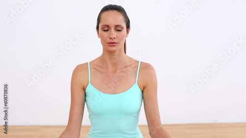 Fit model sitting in lotus pose smiling at camera