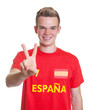 Spanish sports fan with blond hair showing victory sign
