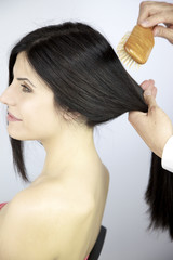 Hairdresser brushing beautiful silky long black hair