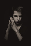 Portrait of pensive teenager on black background