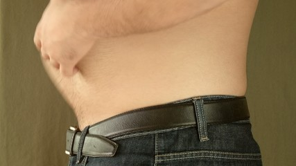 Obese man shakes fat belly. In Jeans.
