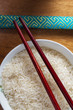 Raw rice in bowl with chopsticks.