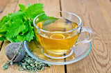 Herbal tea with melissa in a cup and strainer - 60873856