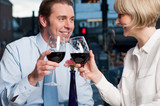 Happy couple raises a glass of red wine