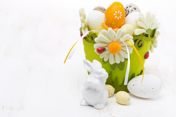 basket with easter eggs and rabbits on white wooden table