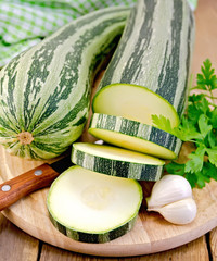 Zucchini green striped with a knife on board