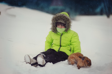 cute boy in green jacket sitting in the snow with a rabbit