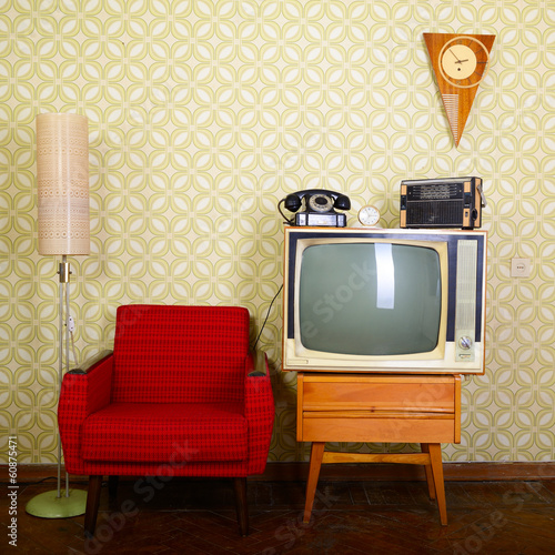 Leinwanddruck Bild Vintage room with wallpaper, old fashioned armchair, tv, phone,