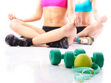 Fitness girl sittingin relax pose with water, dumbbells and meas