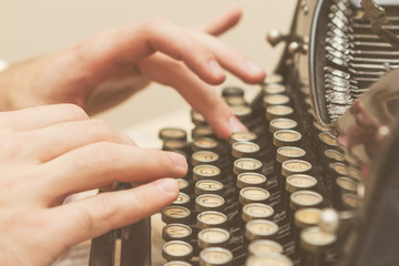 Hands writing on old typewriter