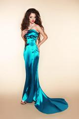 Fashion brunette woman model posing in elegant dress at the stud