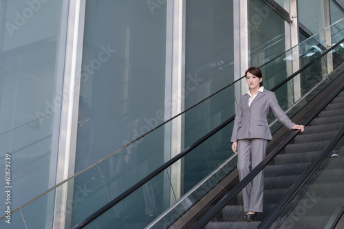 Asian business woman stand at escalator