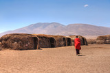 Massai huts with a woman in red in back view
