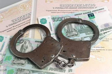 Handcuffs, money on the background of the ownership certificates