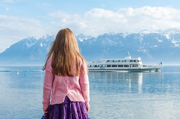 Little girl watching a boat on the lake Geneva