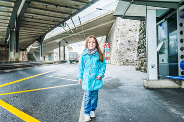 Outddor portrait of a cute little girl on a bus station