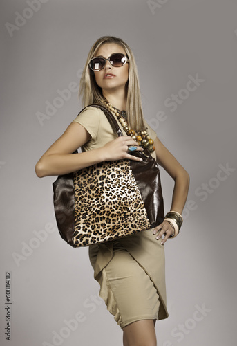 Glamorous blonde woman wearing safari outfit with sunglasses