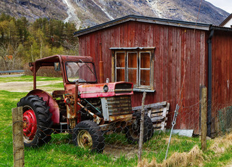Old tractor by wooden house