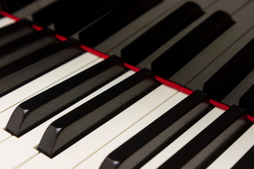 Grand piano keys with reflection in black polished finish