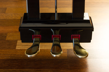 Grand piano pedals over a wooden floor