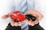 macro red toy car with car keys in mans hand